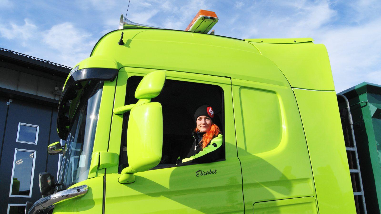 Chauffören Elisabeth sitter i en grön scanialastbil